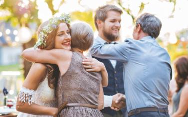 結婚式で両親と抱き合う女性